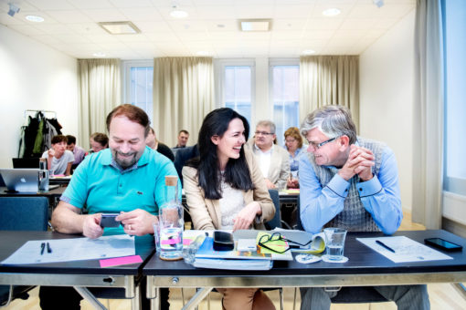 "Three persons discussing and laughing at the conferense ""Innoheat"""