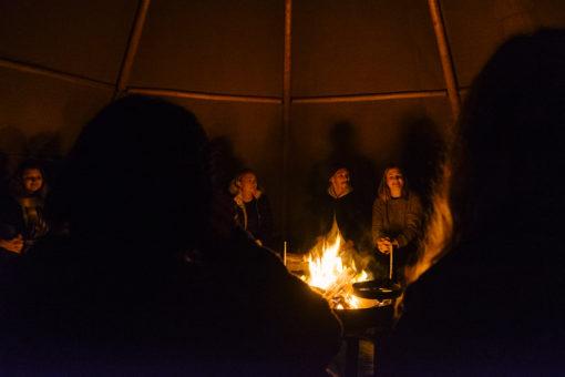 A group of LEAP-participants sitting around an bonfire