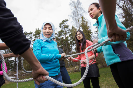 Participants in nature solving a rope excercise