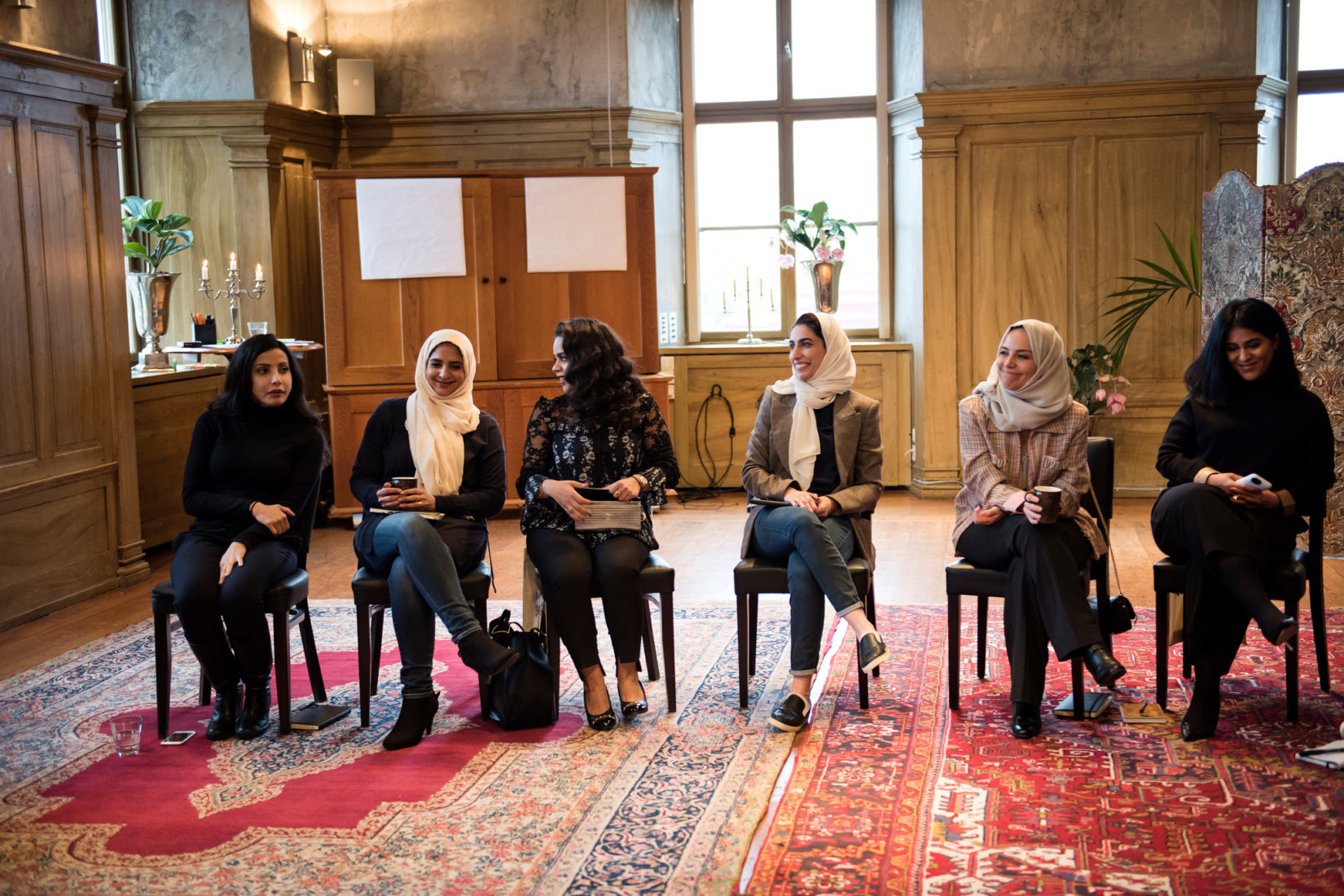 six female entrepreneurs sitting in a row speaking to one another