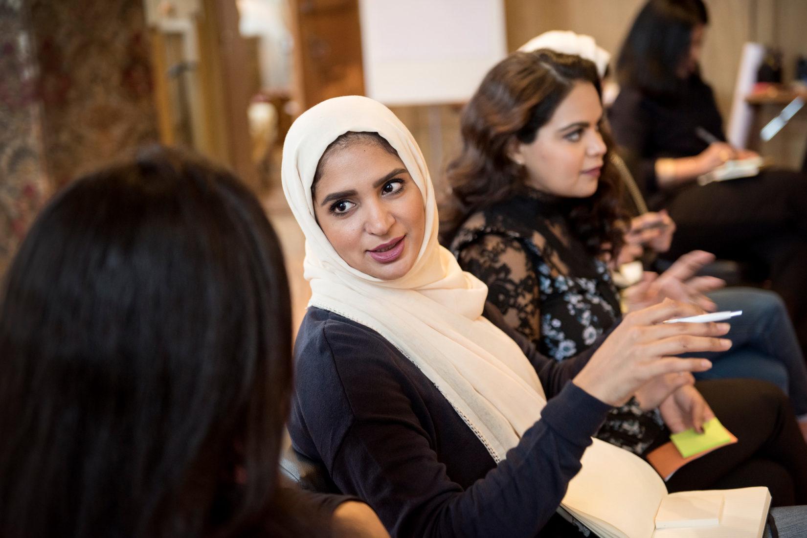 fyra kvinnor i rad sitter i klassrumsmiljö. Fokus på kvinna som talalr med annan kvinna och gestikulerar med händerna.
