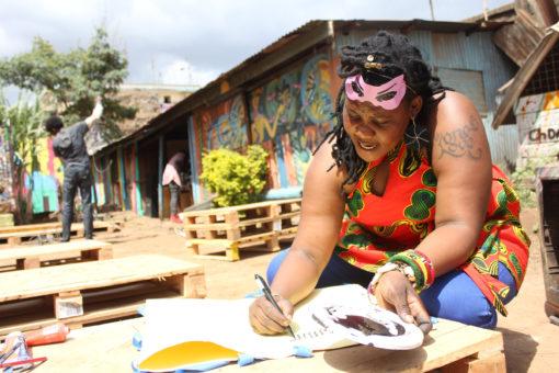 Kvinna sitter utomhus och målar.