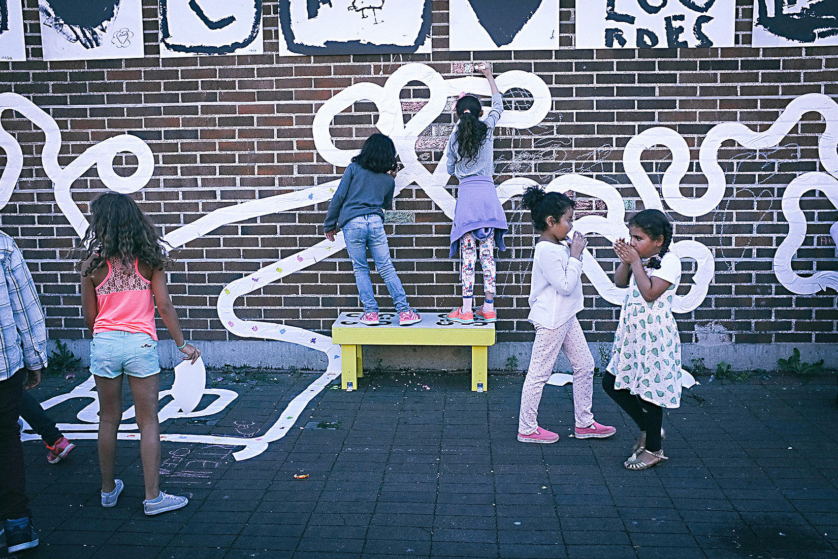 Children playing outsdide and writing on a wall