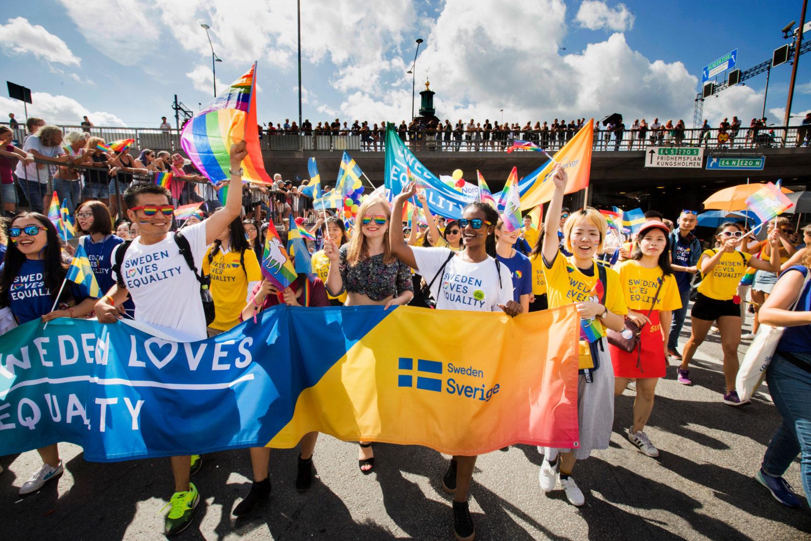 Grupp av människor med regnbågsfärgade banderoller deltar i parad.