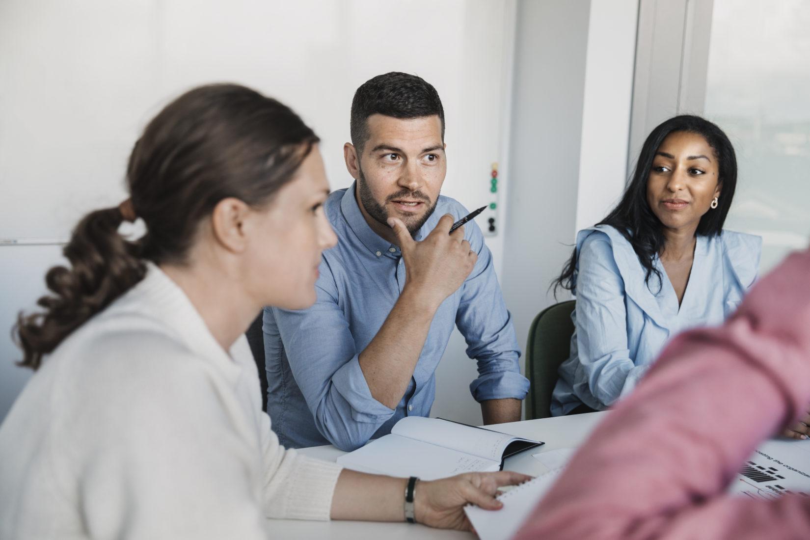 tre personer sitter runt ett bord och pratar