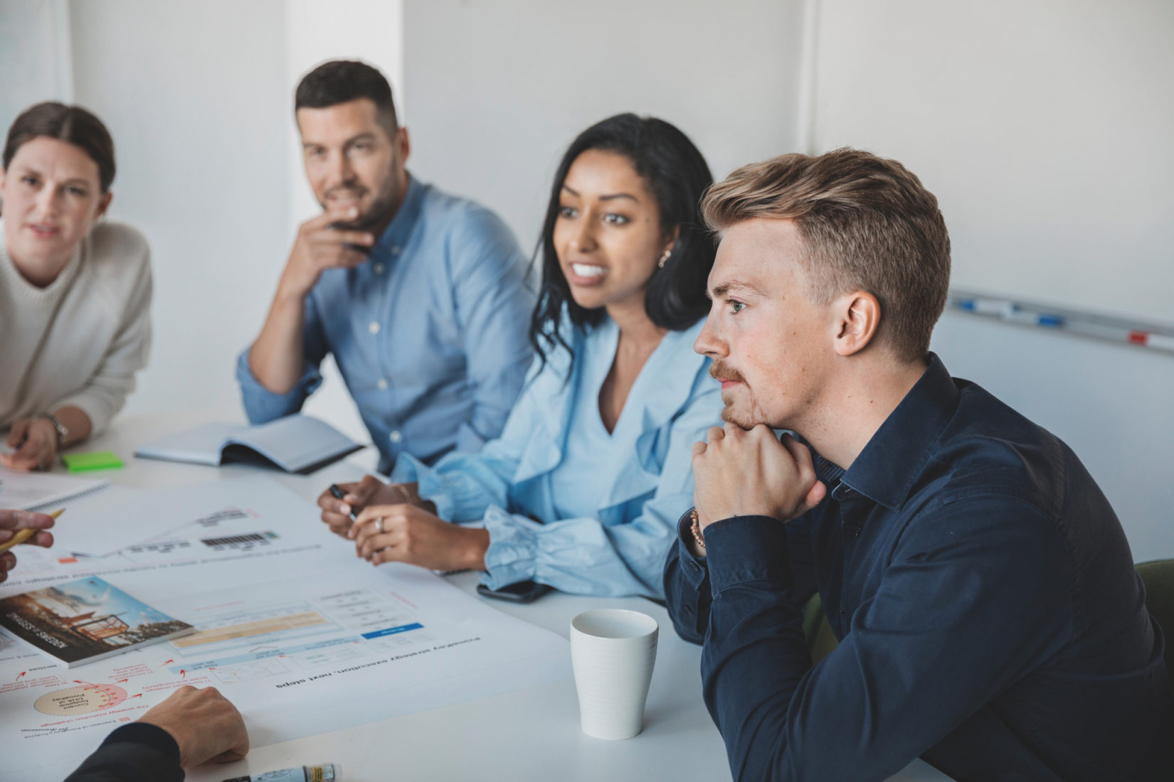 Four persons in a meeting room speaking to one another over a white table. They look very engaged. mix of men and women.