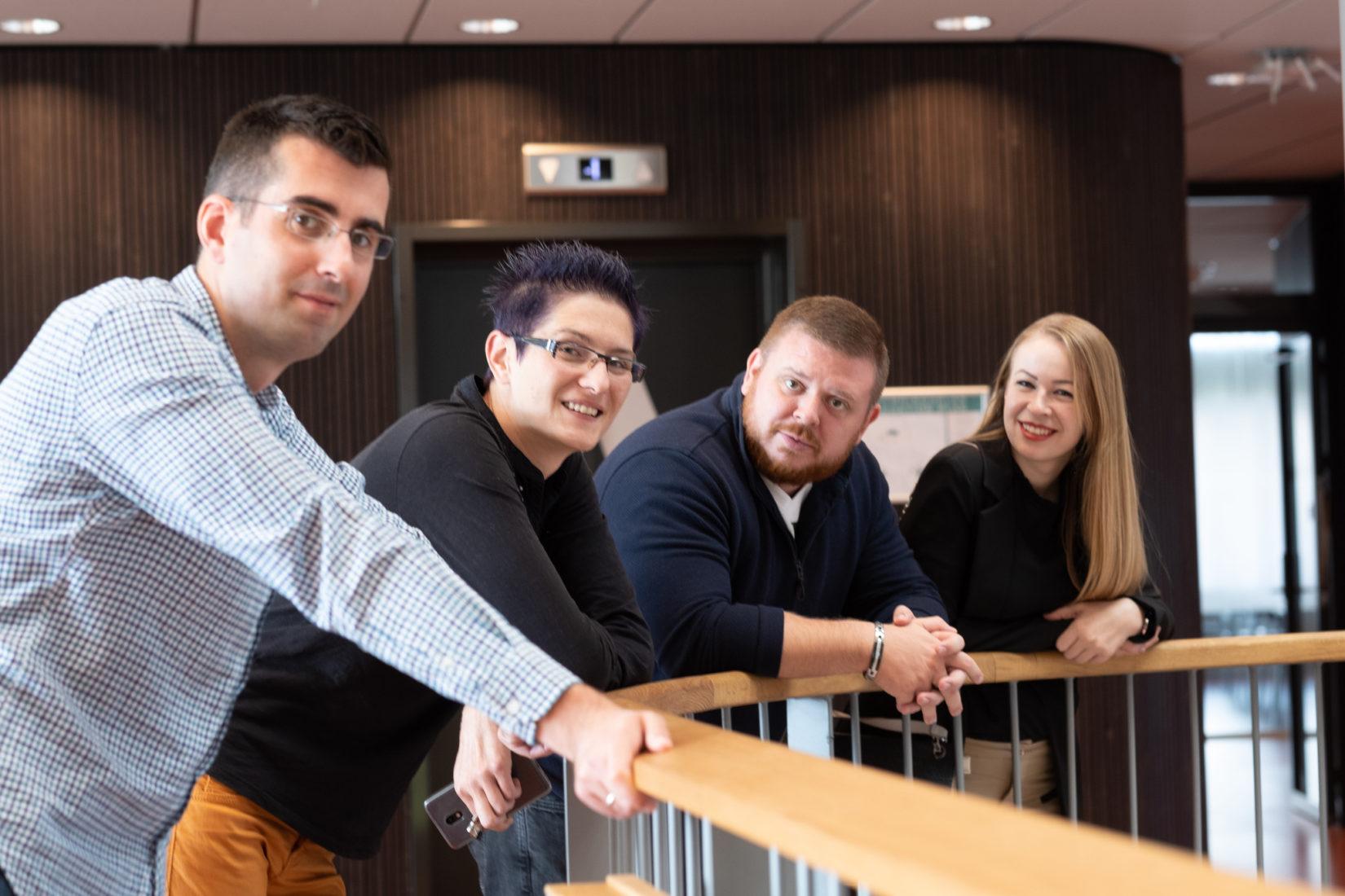 Fyra glada deltagare i ledarskapsprogram står vid ett trappräcke och tittar in i kameran