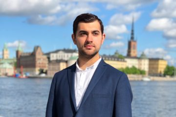 Portrait photo of a young man, with the Stockholm old town in the background.