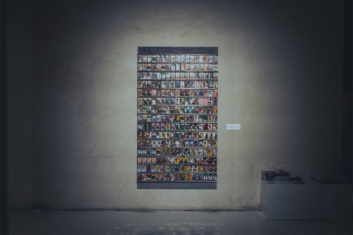 A grey wall with an artwork made with many pictures on it