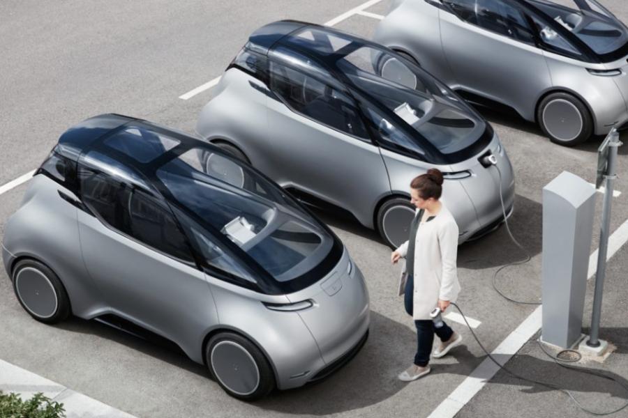 En kvinna går med en laddsladd på en parkeringsplats fram till en väldigt annorlunda bil. Uniti, en bil som sägs vara miljövänlig eller hållbar. Bilen är lättvikt och eldriven, gjort av komposterbara material och energi- och resursoptimerad. Fotograf: Karl-Fredrik von Hausswolff