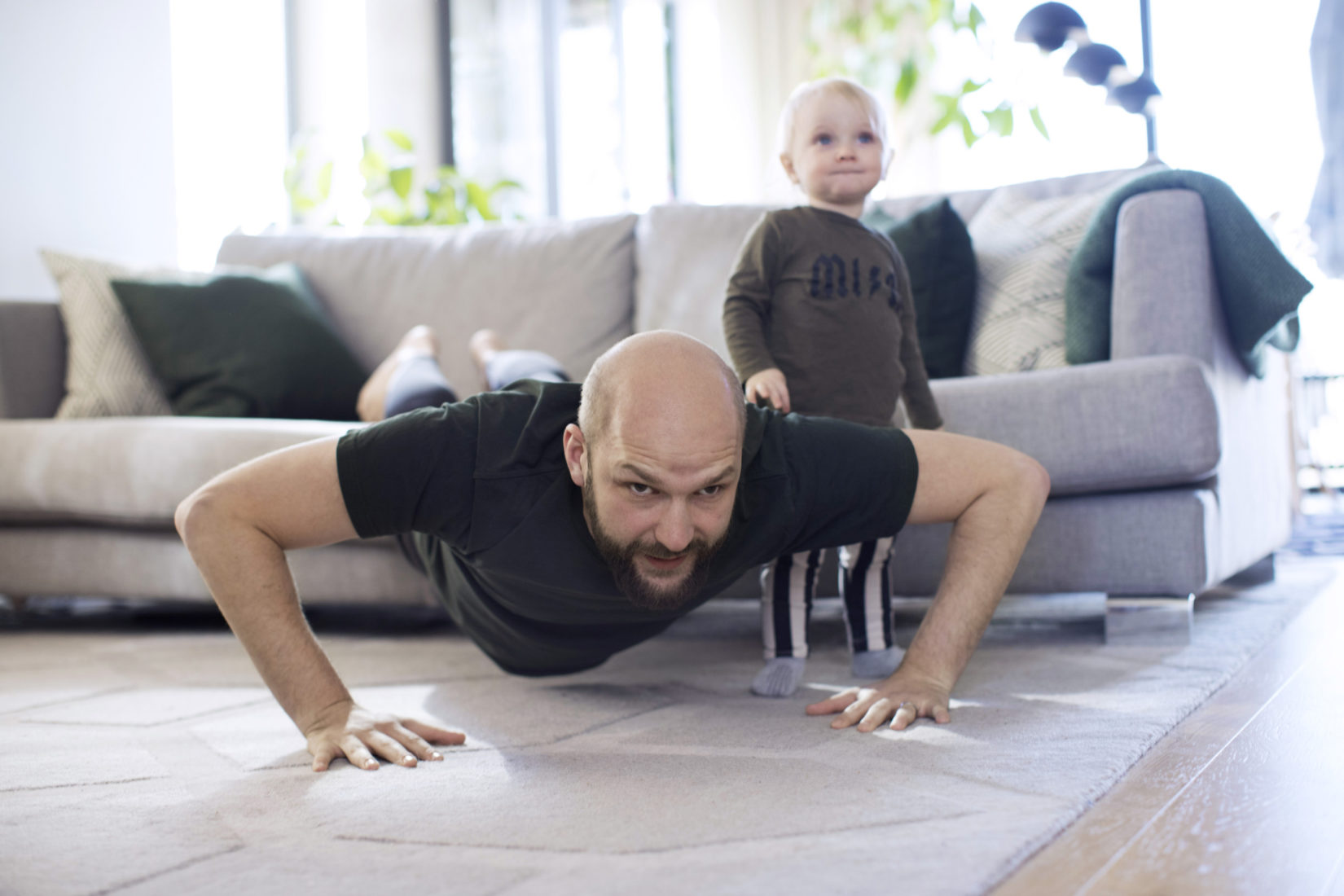 PhDad and child excercising at home on the living room rug