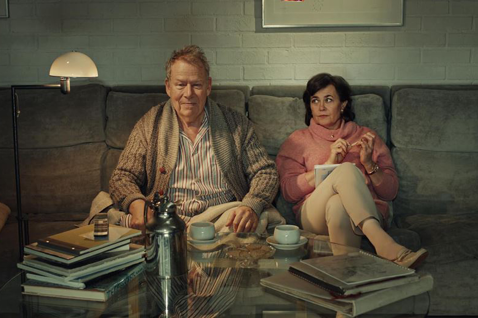 Elderly couple sitting on the sofa drinking coffee