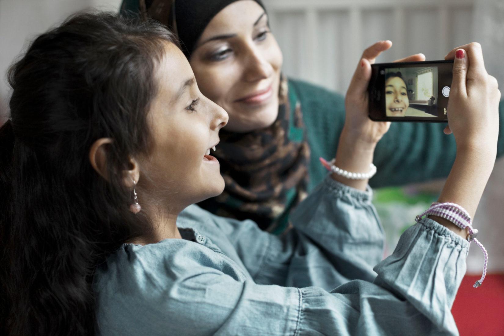 Två flickor tittar på en mobil