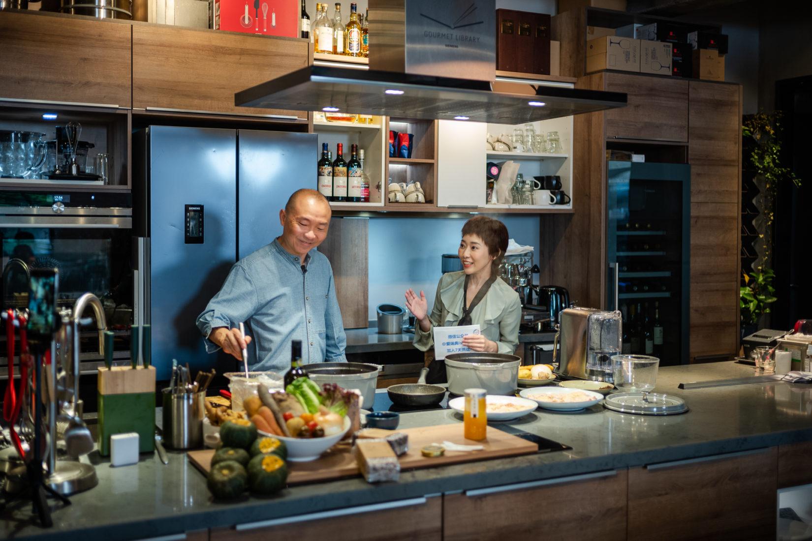 Eat Smart Challenge i Shanghai. Arrangerat av generalkonsulatet. Fotot visar ett kök med en kock som lagar mat och en annan person bredvid som pratar med honom. Fotograf: Zhu Yanxun