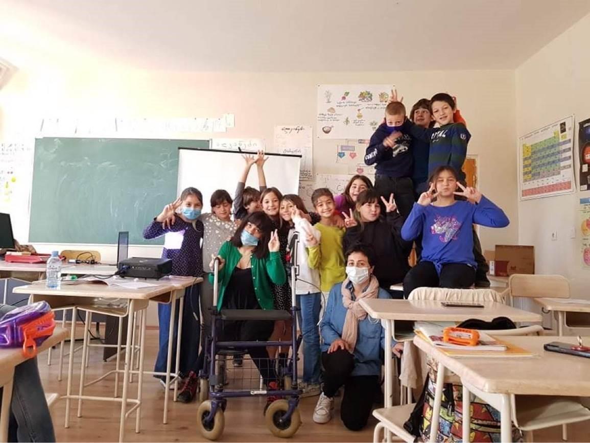 Mariam Kovziridze håller en föreläsning för barn i skola N 21, klass 4 i Tblisi, Georgien. Fotograf: Elene Buadze.  Bilden visar föreläsaren och alla elever glada tillsammans i ett gruppfoto.
