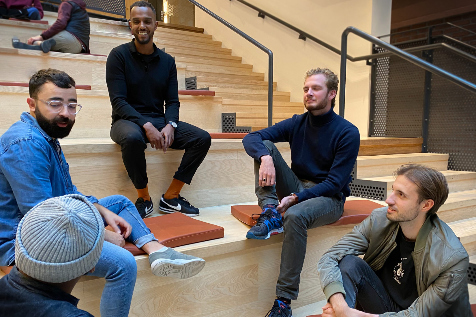 Five men sitting in a stair way construction having a discussion. #globalguytalk aims to bring med together and have discussions around topics they seldom speak about. Photo: Swedish Institute