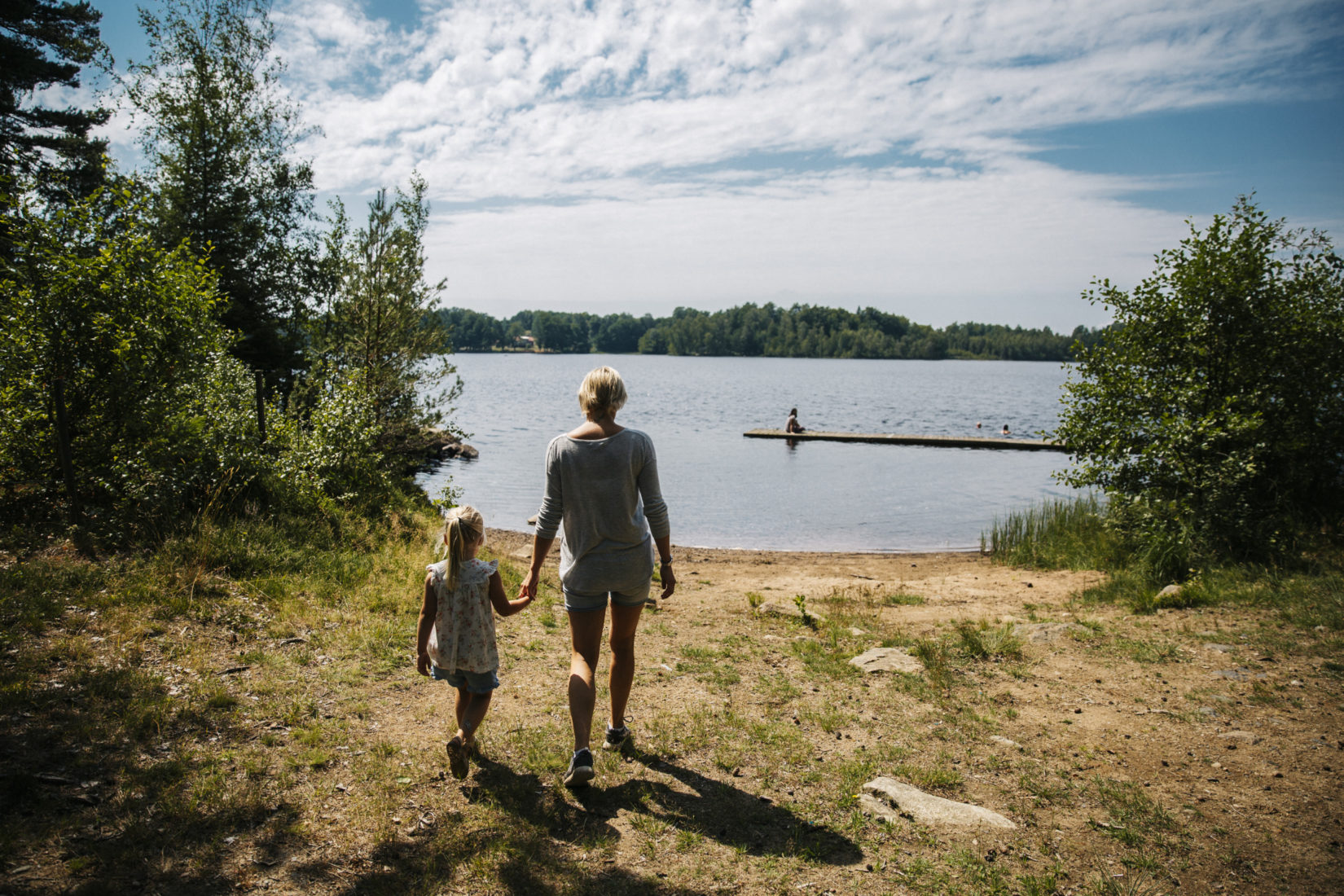 Kid and parent walking to a lake