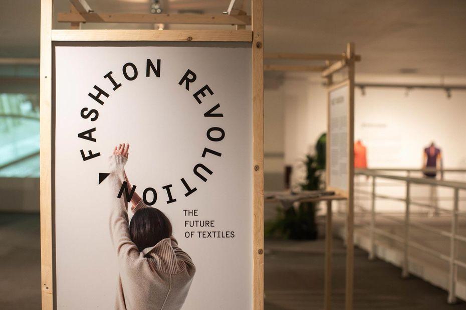Ett foto av den uppbyggda utställningen Fashion revolution - the future of textiles. I en trämodul visas en bild på utställningen logga och ett modefoto med en kvinna bakifrån som sträcker upp armarna. I bakgrunden syns resten av utställningen oskarp.