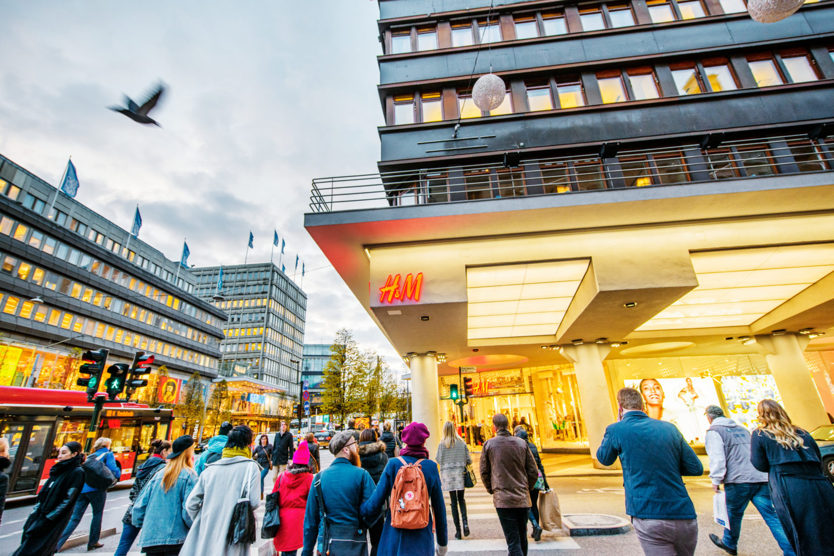 A crowd walking on a shopping street passing an H&M store. The sky is grey and a pigeon is flying right across.
