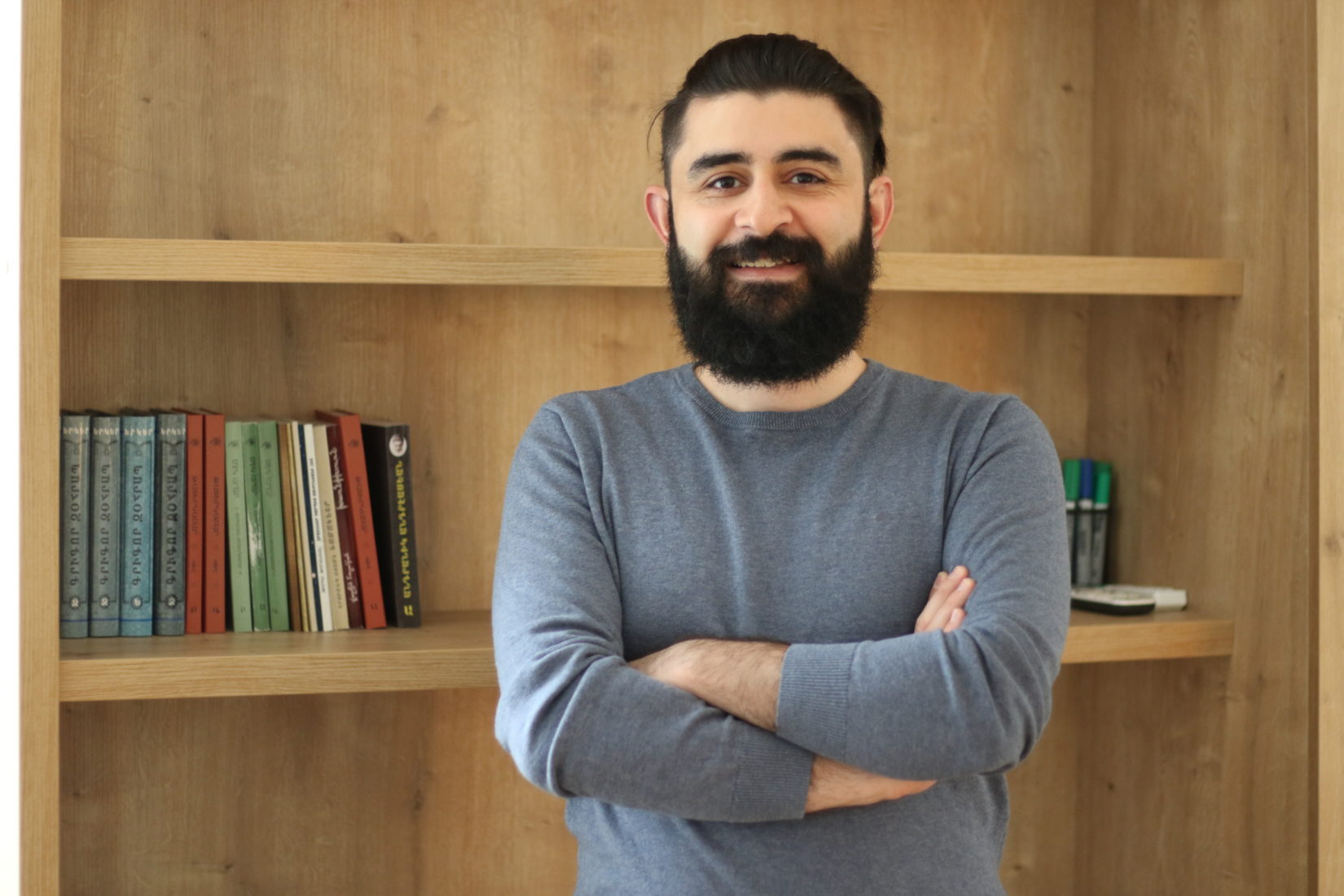 A photo showing a man with dark hair and beard, smiling standing in front of a bookshelf.