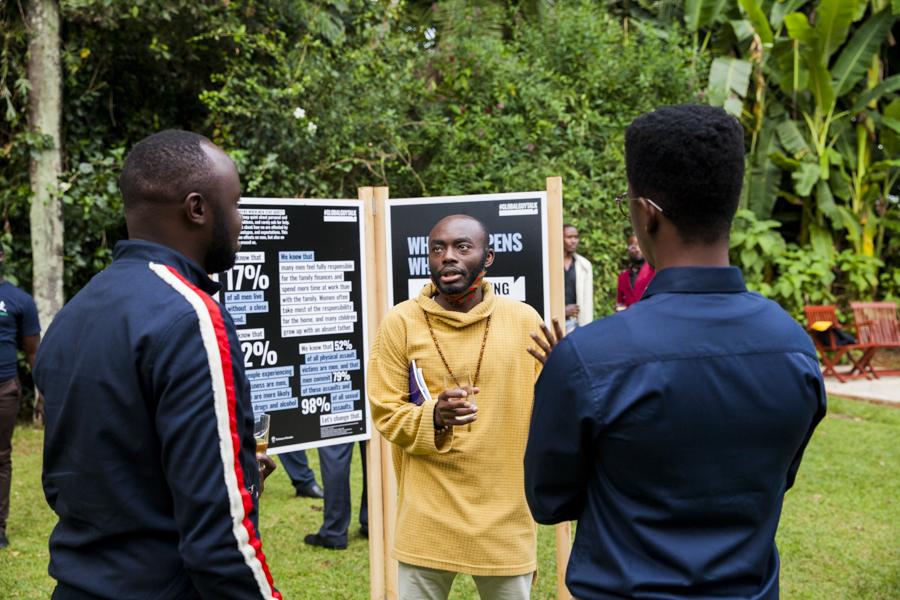 Tre män står utomhus och pratar med varandra.
