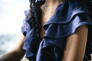 Närbild på en modell med blå klänning med fokus på en draperad volang urringning. Photographer: Margareta Bloom