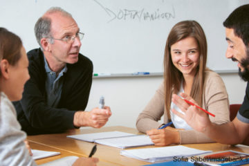 TRe elever och en lärare vid ett bord