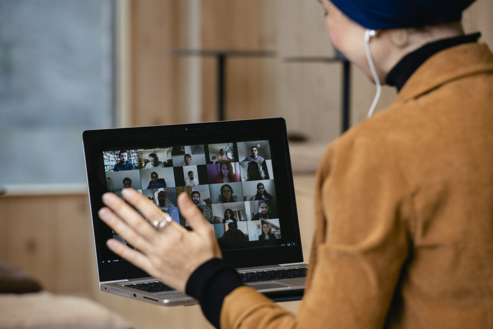 Kvinna framför sitter i ett digital möte framför sin dator