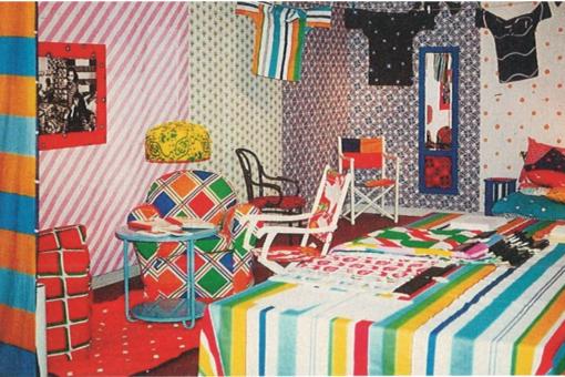 Färgbild från utställning med 10-gruppen från 1974. Föreställer färgglada möbler, kläder och dukar i randigt, prickigt och blommigt.