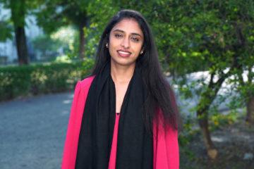 En leende kvinna med långt mörkt hår, iklädd en cerise kappa och en svart sjal står utomhus med träd i bakgrunden.