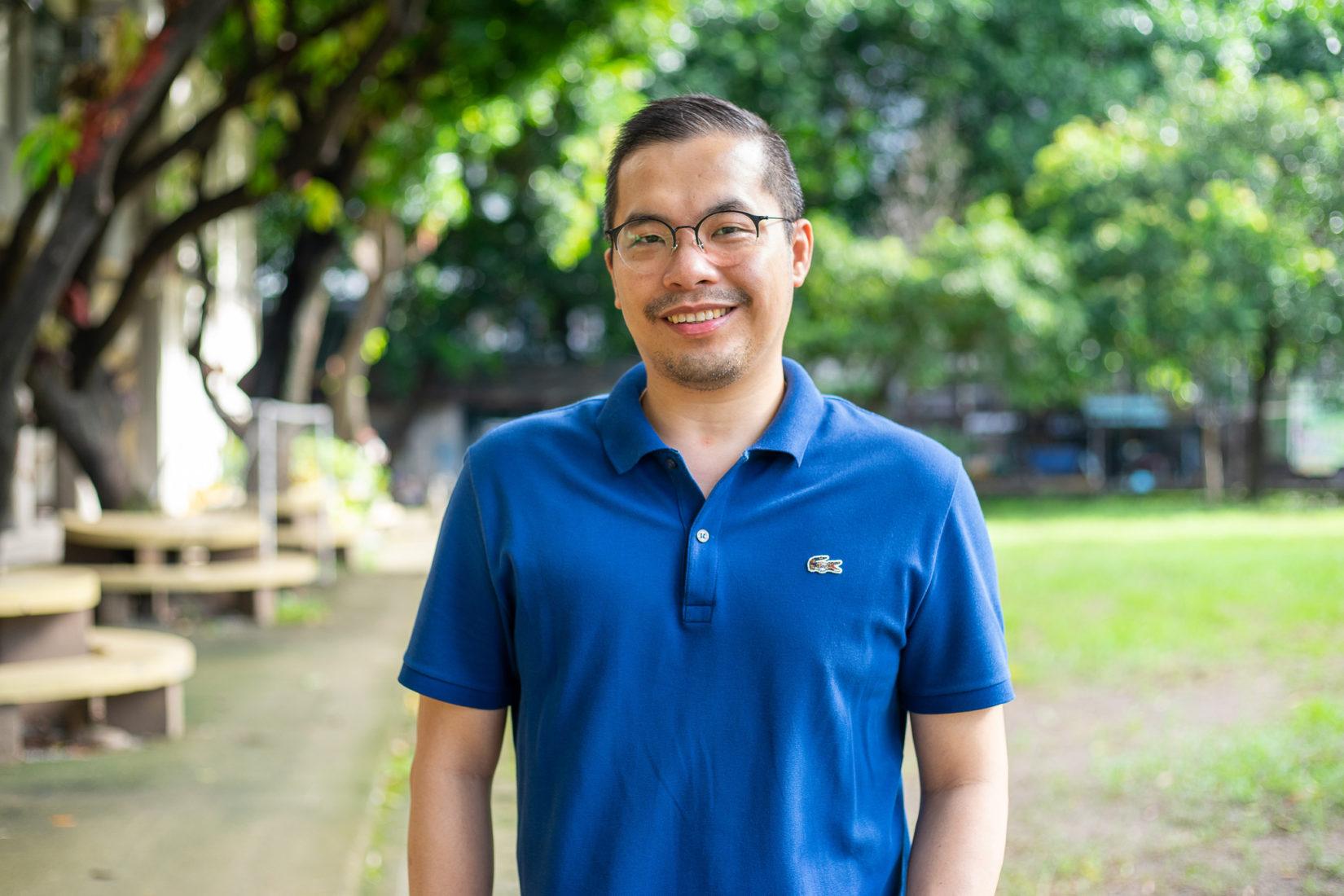 En leende man med glasögon i blå piketröja, står utomhus i en park.