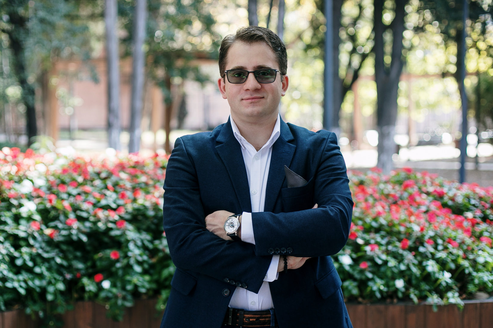 A man in glasses, wearing a suit, smiling, photographed outside in a park.