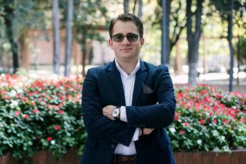 En man i glasögon, iklädd en kostym står med armarna i kors utomhus i en park.