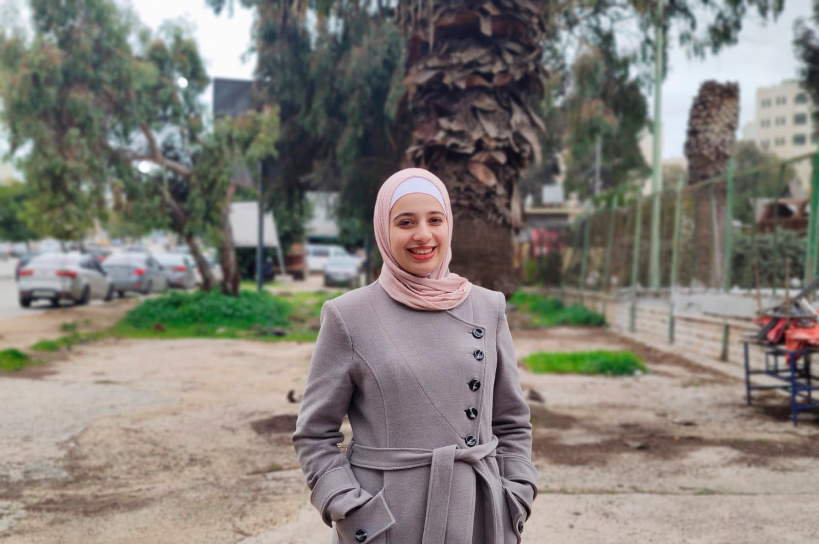 A woman in a grey coat, pink hijab, smiling standing outside in front a a tree.