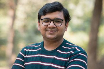 En man med glasögon i en randig tröja som ler och befinner sig utomhus.