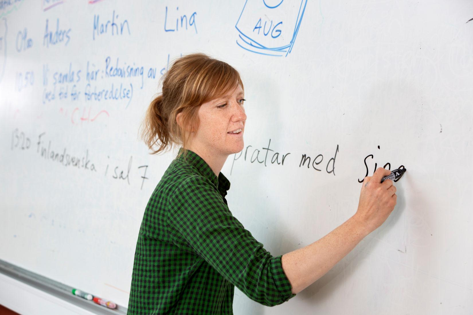 Kvinnlig lärare står och skriver på en vit tavla