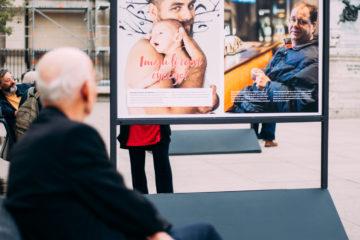 En äldre man sitter på ett torg och tittar på en bild med en barbröstad pappa som håller naken bebis intill sig