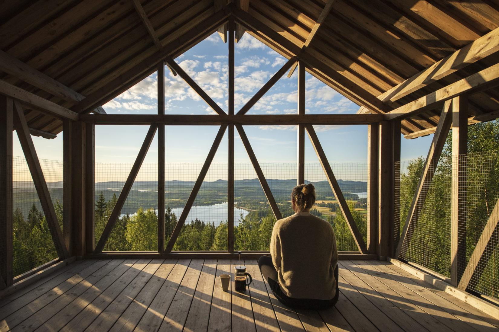 En kvinna sitter med ryggen mot fotografen högt upp i ett hus av trä och tittar ut över skog och himmel