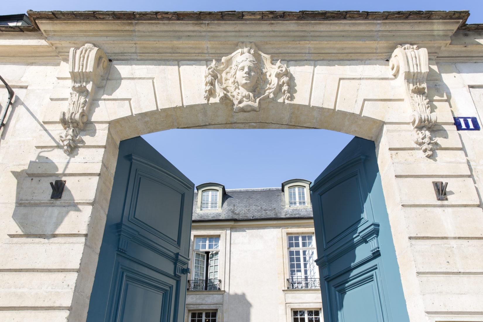 De blå dörrarna till Svenska institutet i Paris står på vid gavel, i bakgrunden skymtar man det vita stenpalatset.