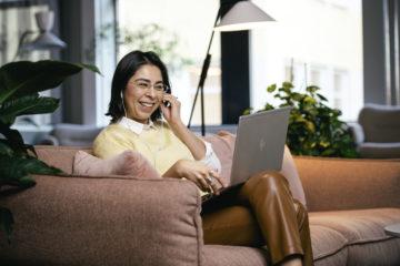 En glad kvinna sitter i en rosafärgadsoffa och pratar i telefon med en uppfäld laptop i knät.