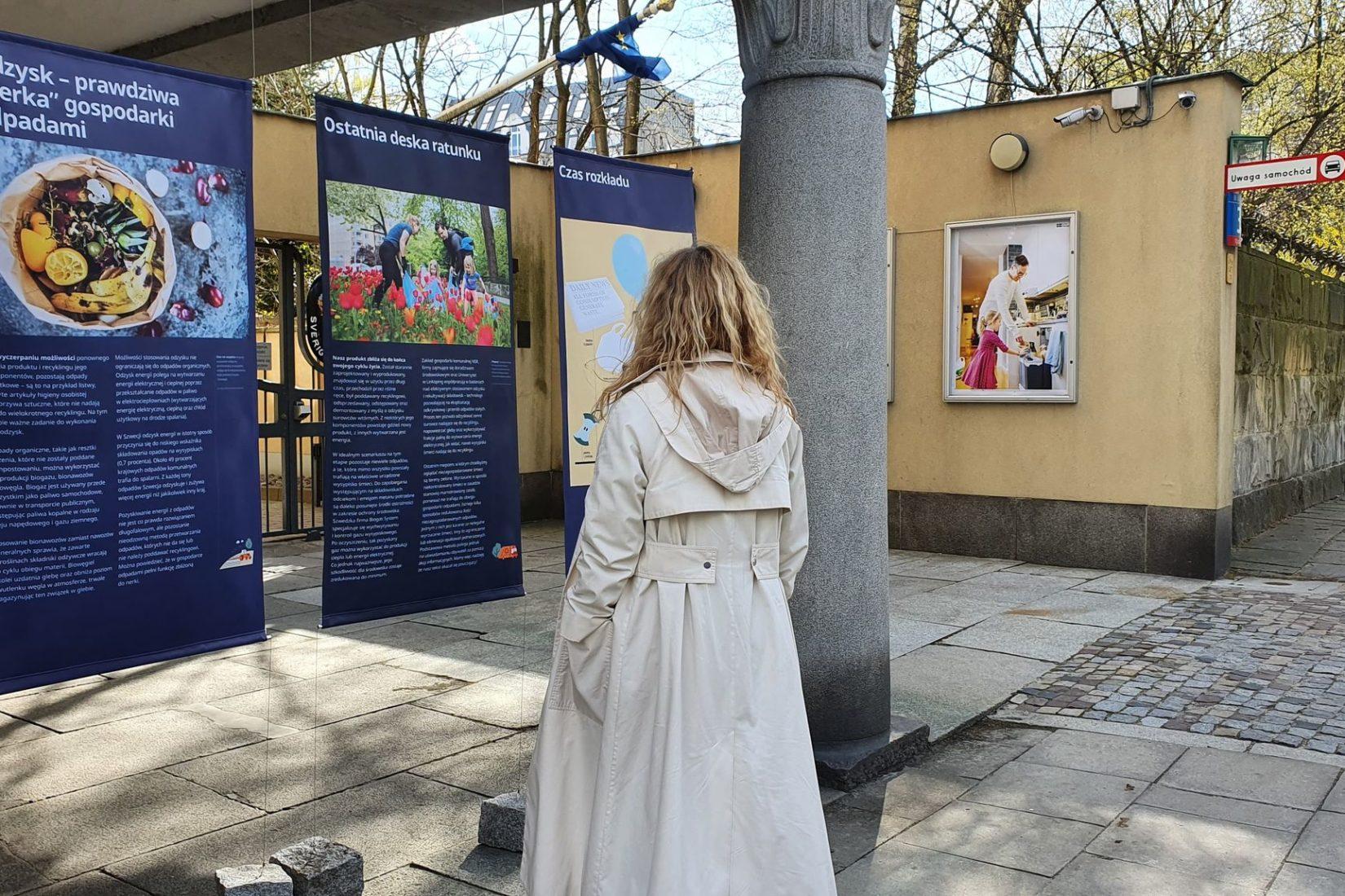 En person med långt blond och lockigt hår med beige trenchcoat tittar på utställningen med ryggen mot kameran.